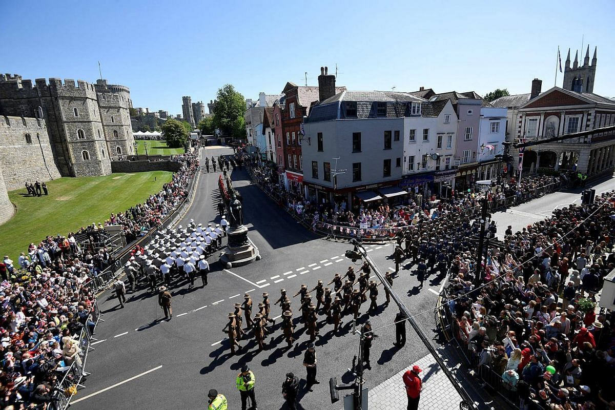 Police officers and members of the public watch as military personnel rehearse their part in the procession, for Britain's Prince Harry and Meghan Markle's wedding, through the streets of Windsor, on May 17, 2018.