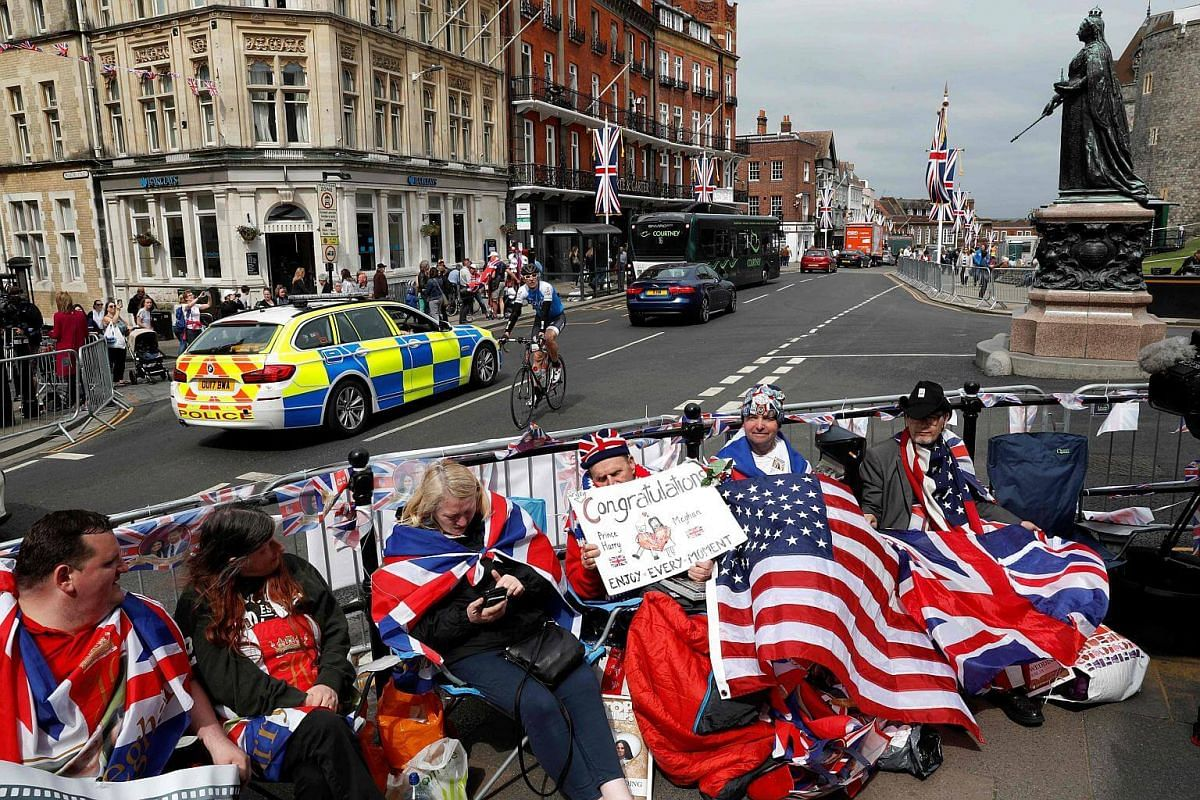 Royal fans, adorned in Union and US flags, sit on a street corner along the wedding procession route to secure their viewing spots for the wedding day, near Windsor Castle in Windsor, on May 16, 2018.