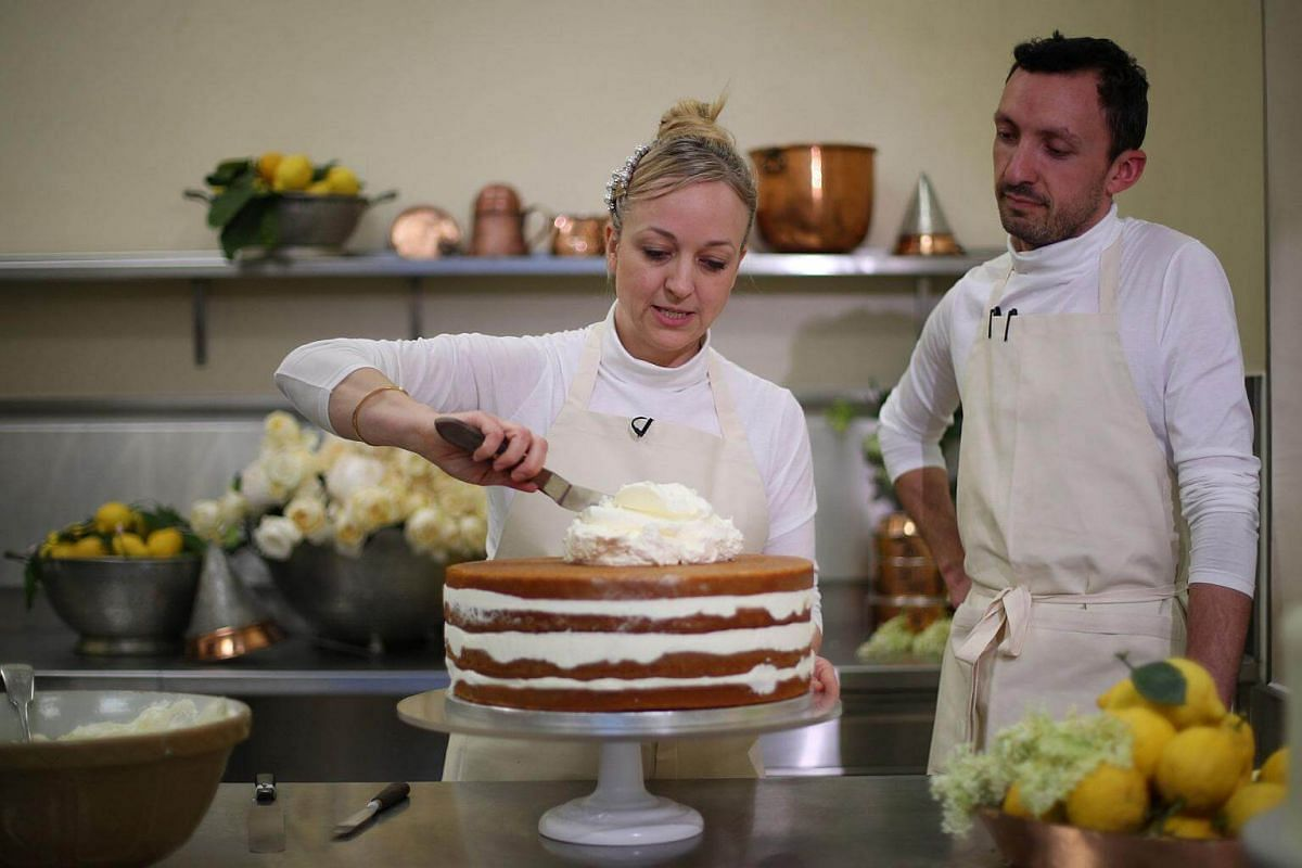 Violet Bakery owner Claire Ptak and head baker Izaak Adams put the finishing touches to the wedding cake of Britain's Prince Harry and Meghan Markle in the kitchens of Buckingham Palace in London, on May 17, 2018.