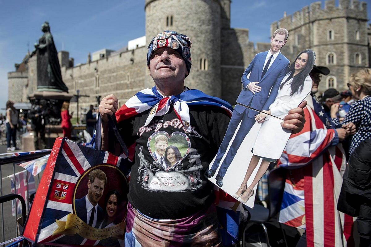 A royal family fan poses with memorabilia for photographs outside Windsor Castle in Windsor, on May 17, 2018.