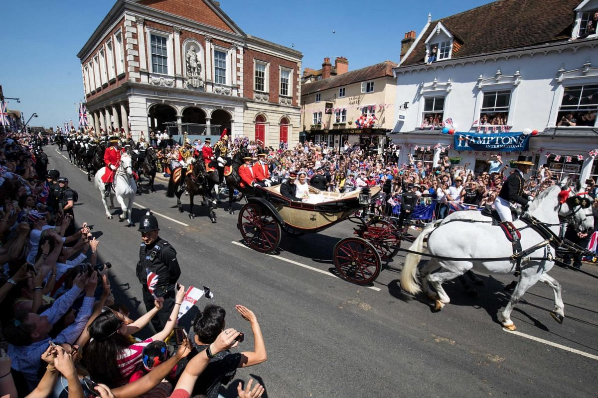 Britain's Prince Harry and his wife Meghan Markle ride in a horse-drawn Ascot Landau carriage during a procession after their royal wedding ceremony in Windsor on May 19, 2018.