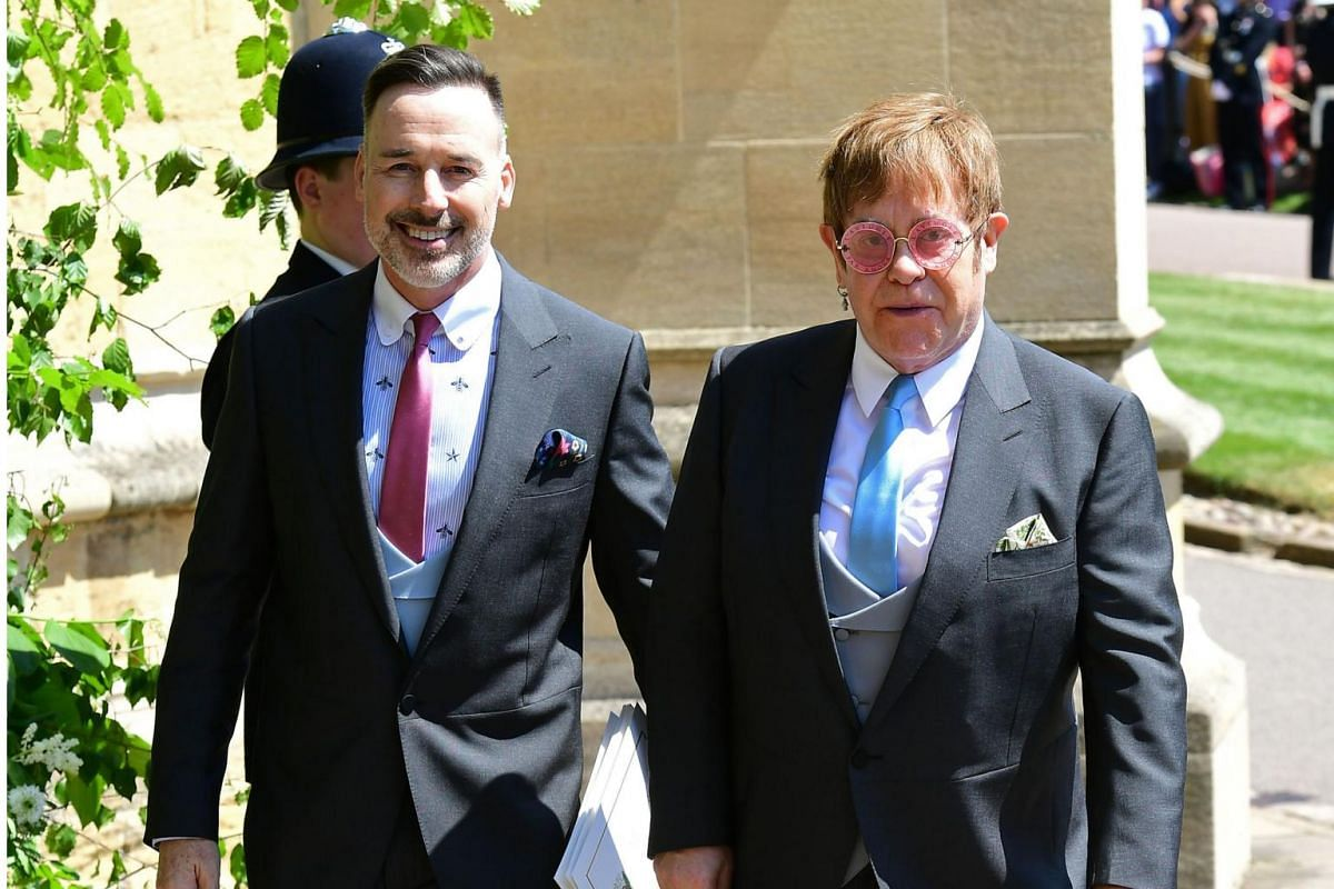 British singer-songwriter Elton John and his husband David Furnish leave after attending the wedding ceremony of Britain's Prince Harry and US actress Meghan Markle at St George's Chapel at Windsor Castle on May 19, 2018.