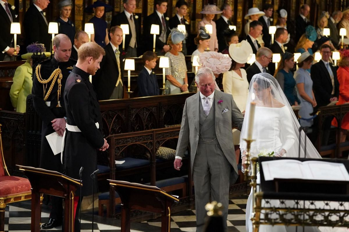 Britain's Prince Harry looks at his bride, Meghan Markle, as she arrives accompanied by Britain's Prince Charles in St George's Chapel at Windsor Castle on May 19, 2018.