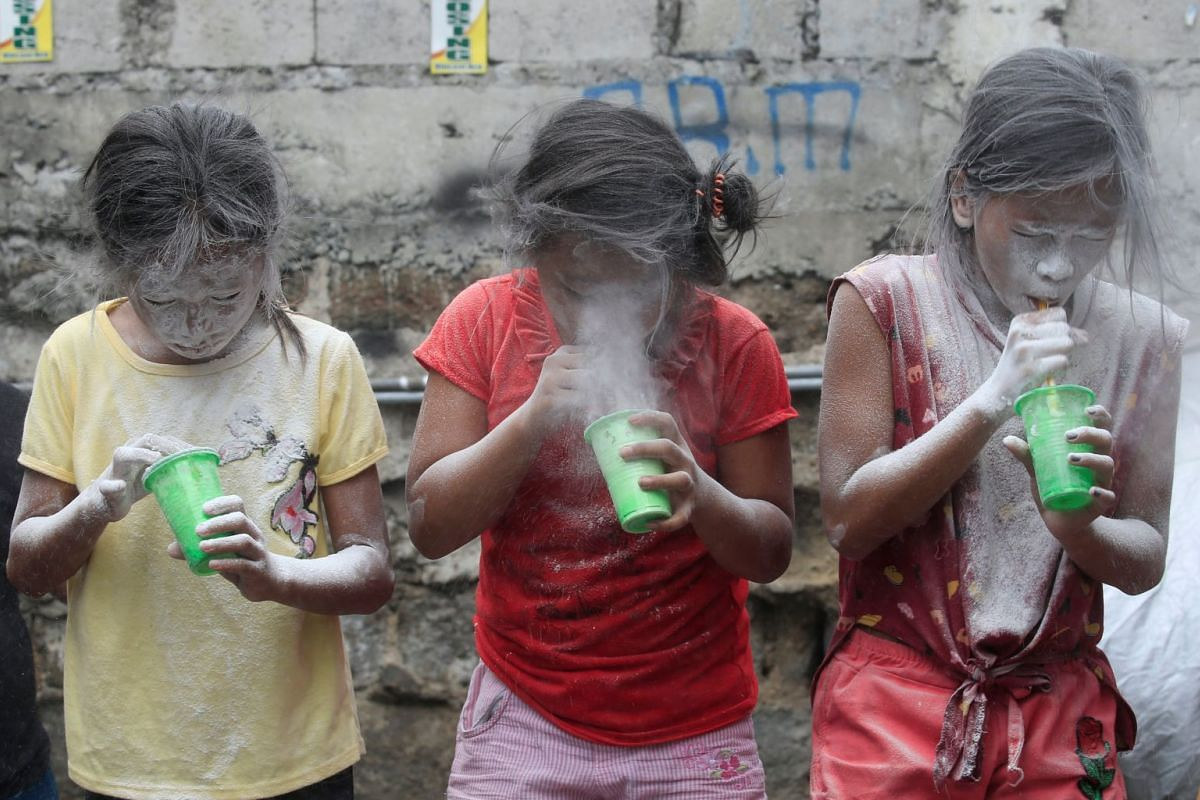 Girls' faces are covered by white powder after blowing it, at a town fiesta parlour game, in celebration of patron saint Santa Rita de Cascia in Baclaran, Paranaque City, Metro Manila, Philippines, May 20, 2018.
