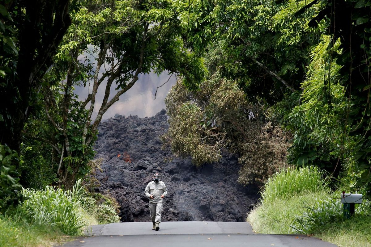Lieutenant Colonel Charles Anthony, of the Hawaii National Guard, measures sulfur dioxide gas levels at a lava flow on Highway 137 southeast of Pahoa during ongoing eruptions of the Kilauea Volcano in Hawaii, U.S., May 20, 2018.