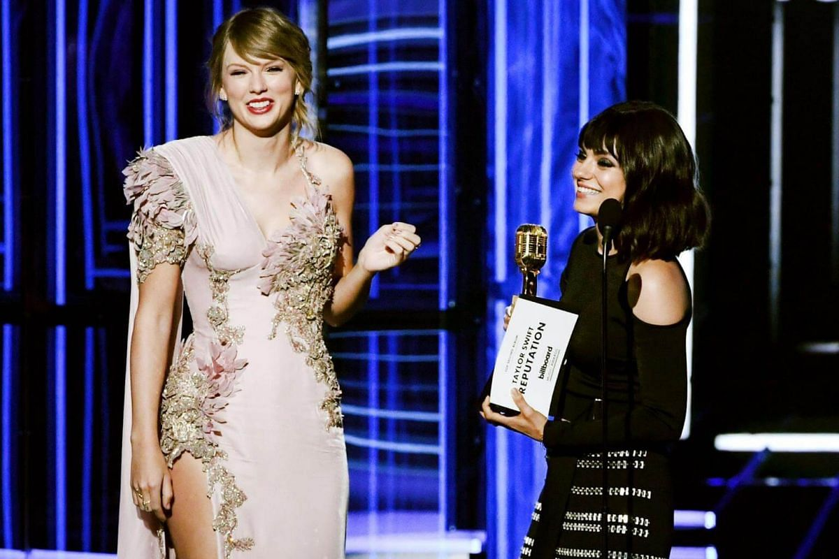 Taylor Swift (left) accepts the Top Selling Album award for Reputation from Mila Kunis onstage during the 2018 Billboard Music Awards, on May 20, 2018.