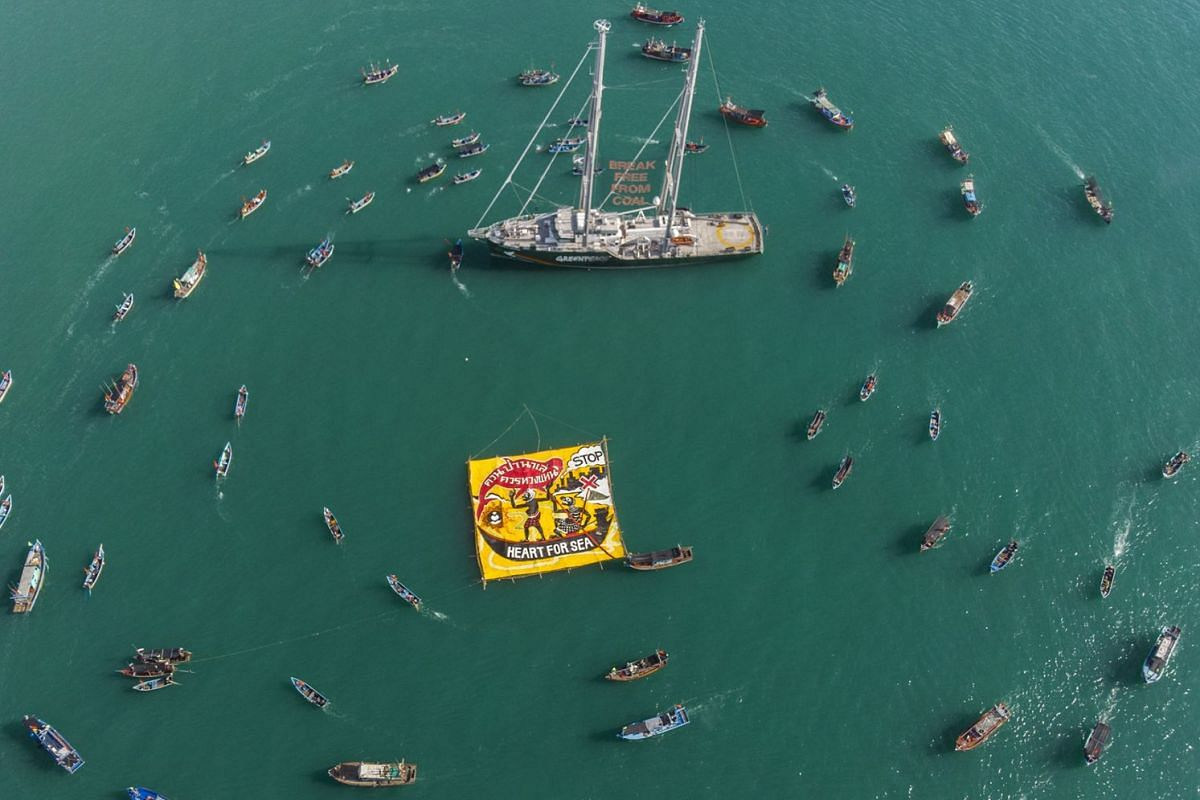 A handout photo made available by Greenpeace shows boats circling the Rainbow Warrior during a protest against a coal-fired project in the Gulf of Thailand near Songkhla province, Thailand, May 21, 2018. Greenpeace's Rainbow Warrior is currently on i