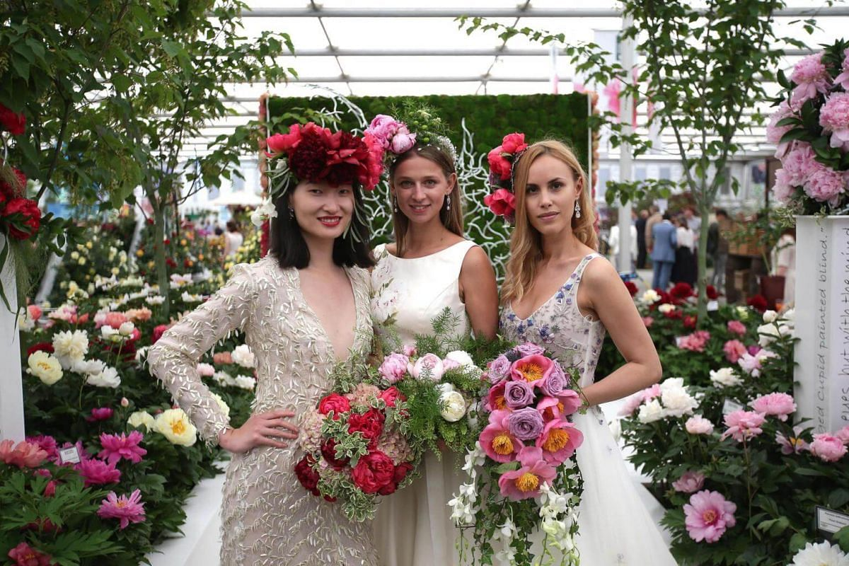 Models pose for a photograph as they stand at the Primrose Hall peony display during a visit to the 2018 Chelsea Flower Show, on May 21, 2018.