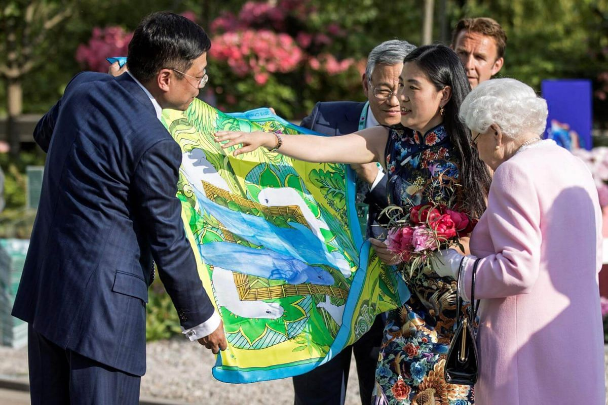 Britain's Queen Elizabeth II (right) is presented with a Chinese silk scarf after she looked at the Chinese show garden, on May 21, 2018.