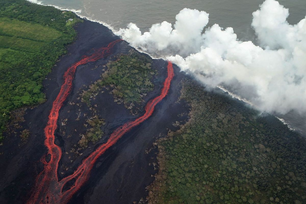 Steam plumes rise as lava enters the Pacific Ocean, after flowing to the water from a Kilauea volcano fissure, on Hawaii's Big Island on May 21, 2018 near Pahoa, Hawaii. Officials are concerned that 'laze', a dangerous product produced when hot lava