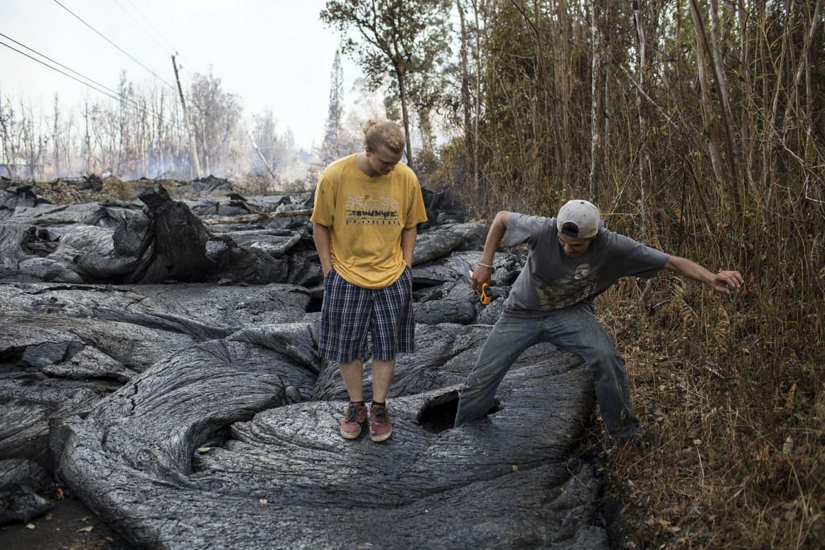 Brandon Lofgreen (left) stands beside Thomas Robinson as he kicks a hole through recently hardened lava from a Kilauea volcano fissure that flowed over a street in the Leilani Estates neighborhood, near Pahoa, Hawaii, May 22, 2018. Since early May, t
