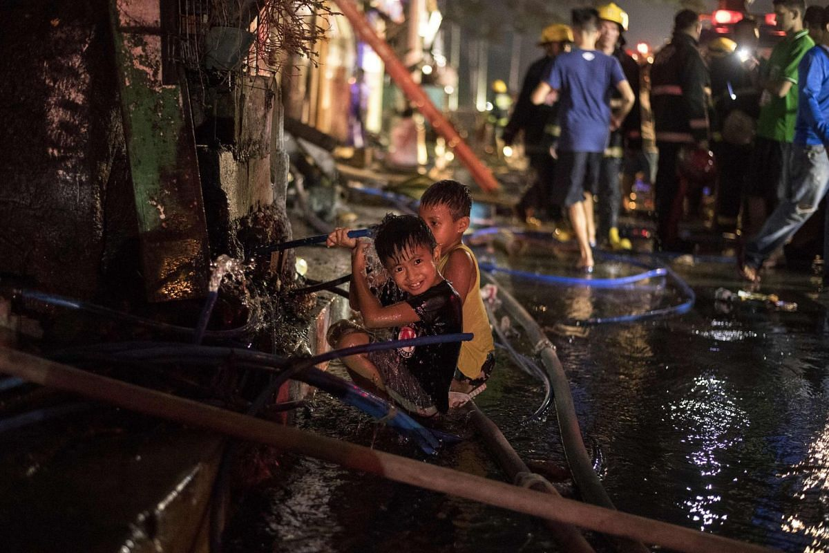Children play with a busted water hose as a fire engulfes a slum area in Manila on May 23, 2018. The fire destroyed 200 houses affecting 300 families according to local media.