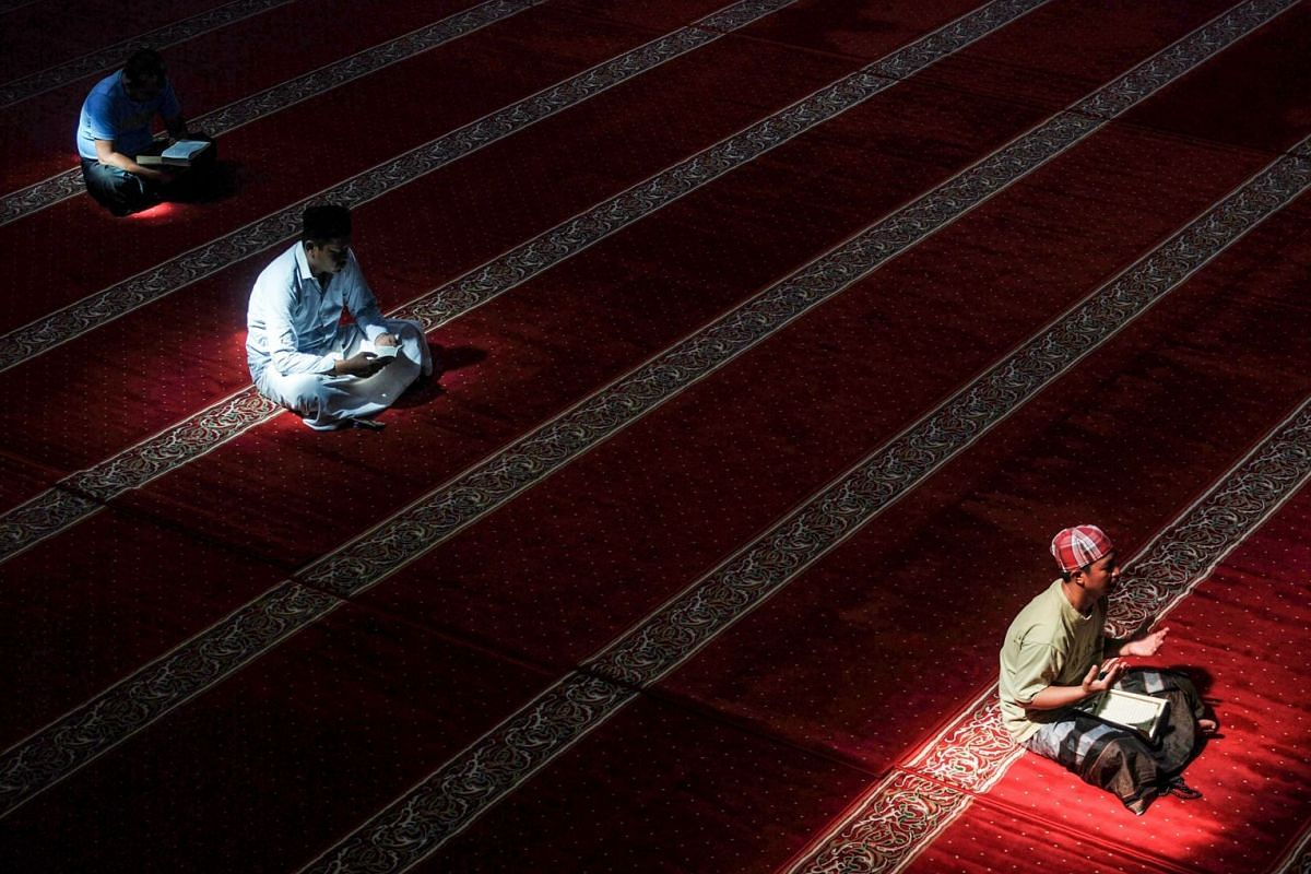 Indonesian Muslims read the Koran at a Mosque in Bandung, West Java, on May 23, 2018, during the month of Ramadan. Muslims throughout the world are marking the month of Ramadan, the holiest month in the Islamic calendar during which devotees fast fro