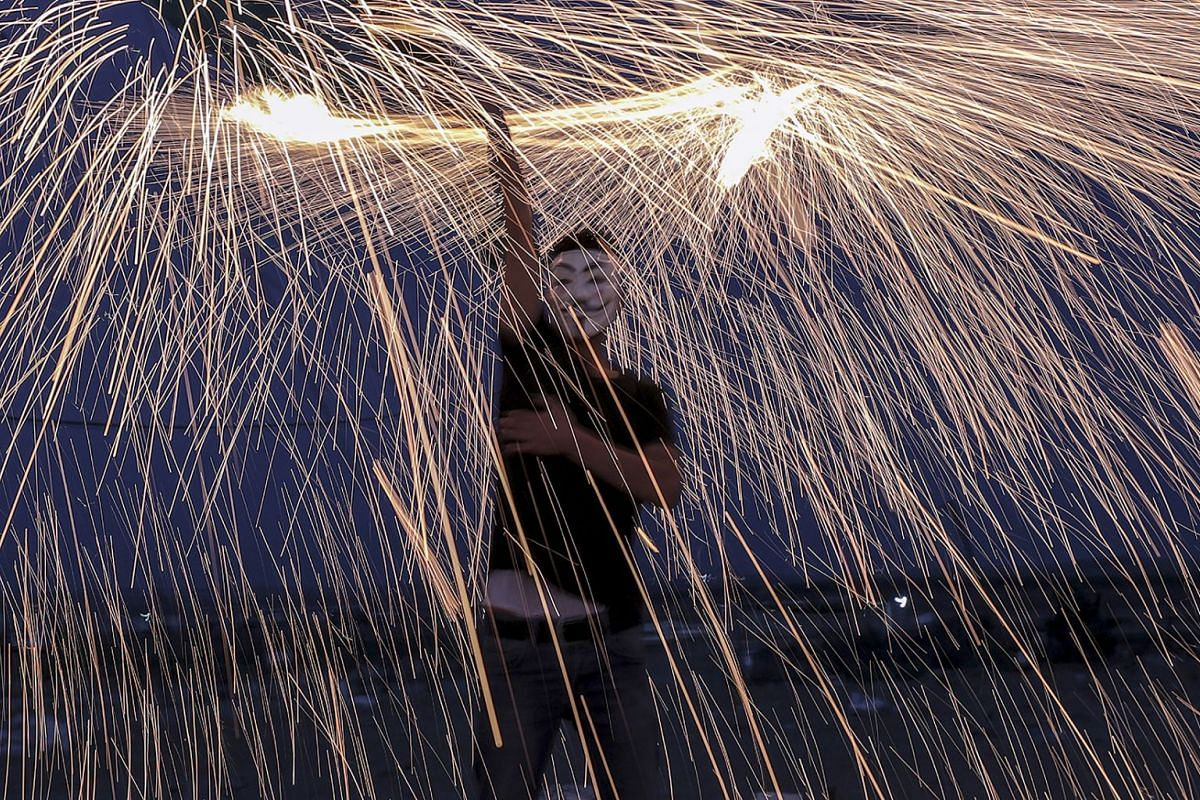 A Palestinian protester puts on a fireworks display next to the border between Israel and east Gaza Strip during the holy month of Ramadan in Gaza City, Gaza Strip, May 24, 2018. A group of Palestinians youths lit fireworks as a protest against Israe