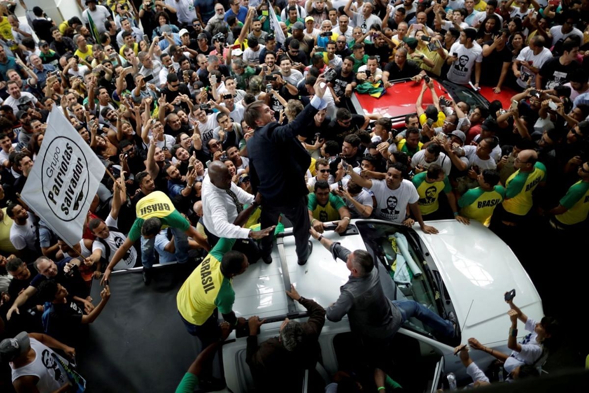 Federal deputy Jair Bolsonaro, a pre-candidate for Brazil's presidential election, is greeted by supporters as he arrives at Luis Eduardo Magalhaes International Airport in Salvador, Brazil on May 24, 2018.