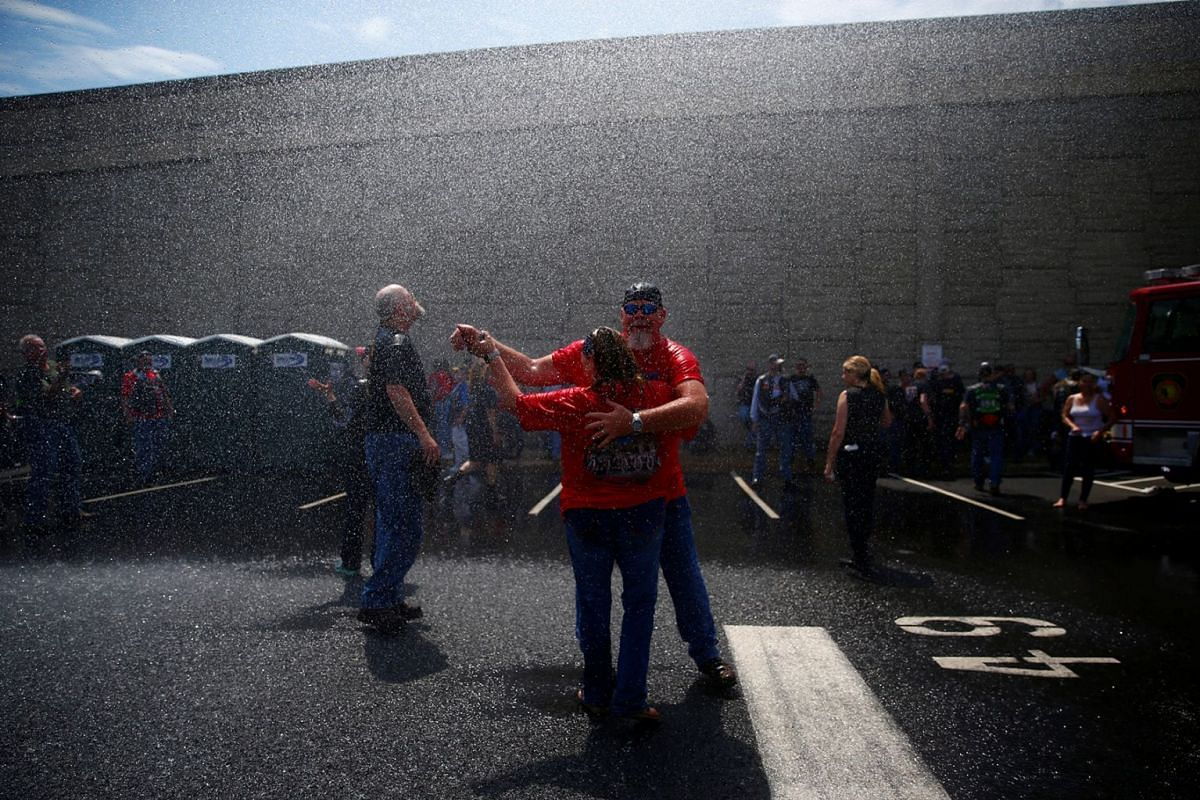 Two people dance under the spray from a fire engine hose, as participants gather in the parking lot of the Pentagon as thousands of military veterans and their supporters participate in the 31st annual Rolling Thunder motorcycle rally and Memorial Da