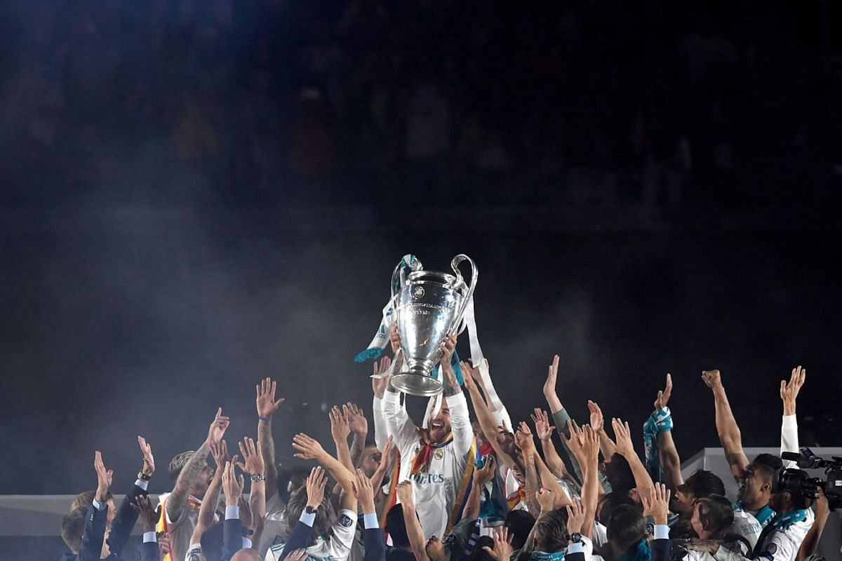 Real Madrid's Spanish defender Sergio Ramos (C) lifts the trophy as he celebrates with teammates at the Santiago Bernabeu stadium in Madrid on May 27, 2018 during a victory ceremony after Real Madrid won its third Champions League title in a row in K