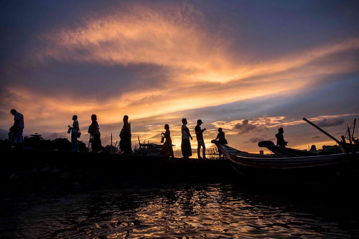 People arrive at a jetty to cross the Yangon River on boats during sunset in Yangon on May 26, 2018. Photo: AFP