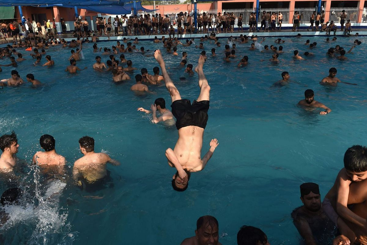 Pakistani youth cool down at a swimming pool during a a hot day in Lahore on May 27, 2018. Photo: AFP
