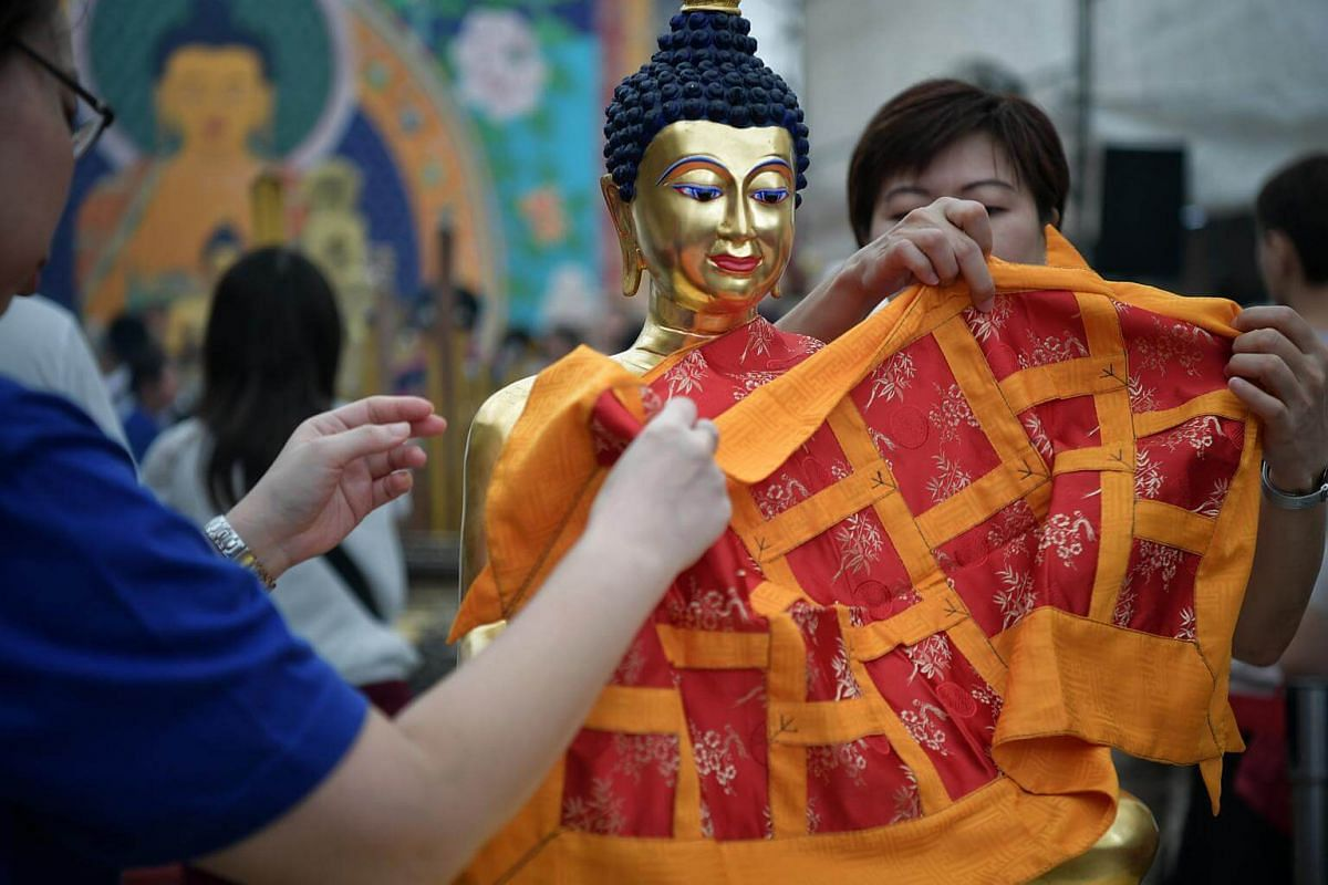 Devotees practicing the offering of robes at Thekchen Choling on Vesak Day, which falls on May 29, 2018.
