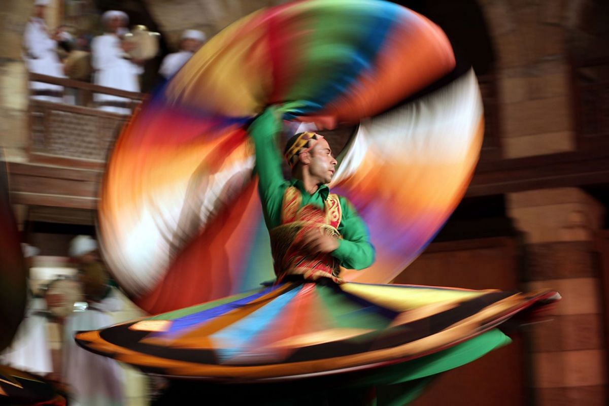 Egyptian dancers spinning a tanoura skirt during Ramadan Festival at Al Ghoury Palace in Cairo, Egypt, early on May 30 2018. Al Tanoura is usually practiced by Sufi Muslims and is a spiritual practice where spinning and discarding three skirts repres