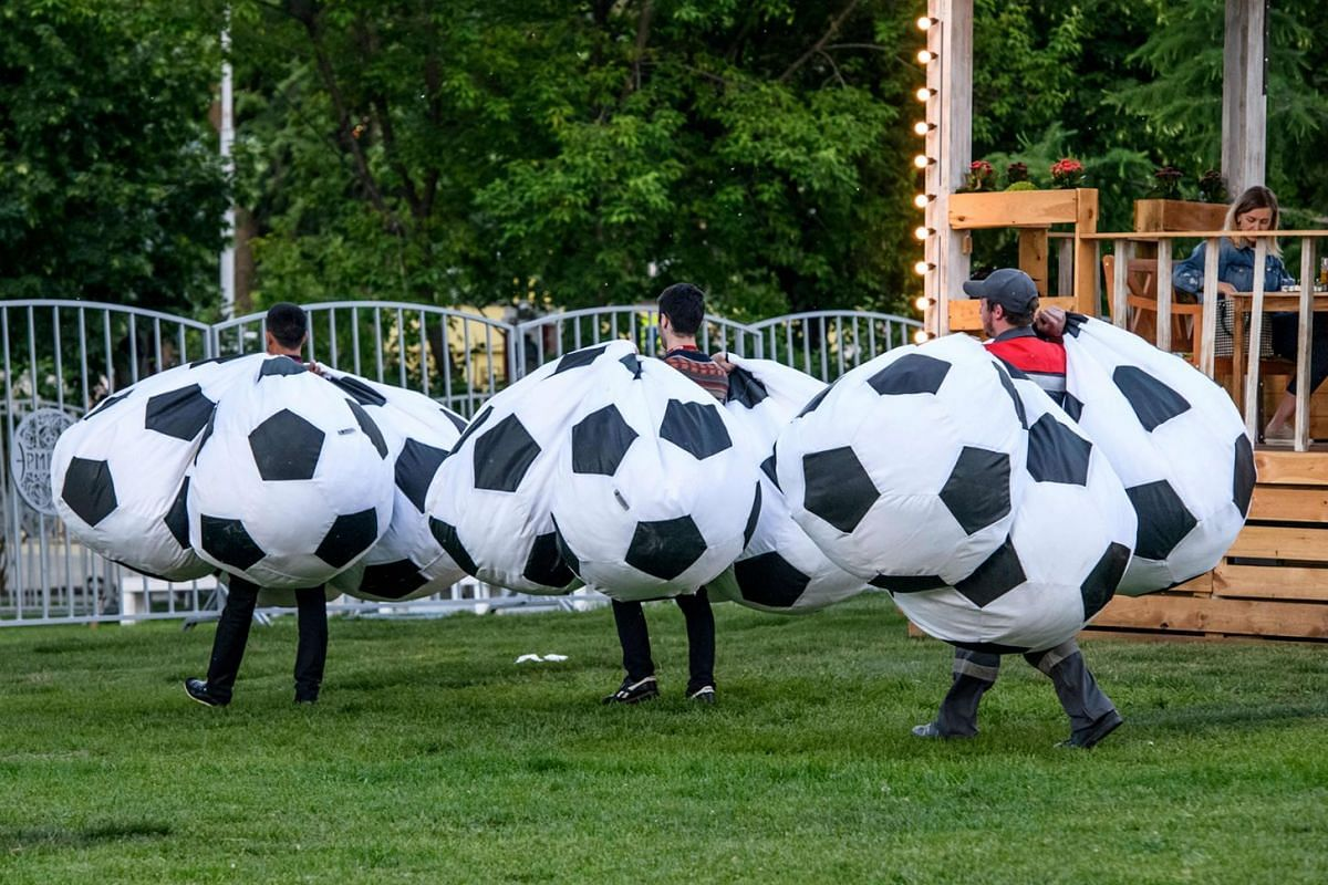 Workers carry football-themed bean bags for an outdoor cinema in a park in central Moscow on May 29, 2018. The FIFA World Cup 2018 in Russia tournament kicks off on June 14. Photo: AFP