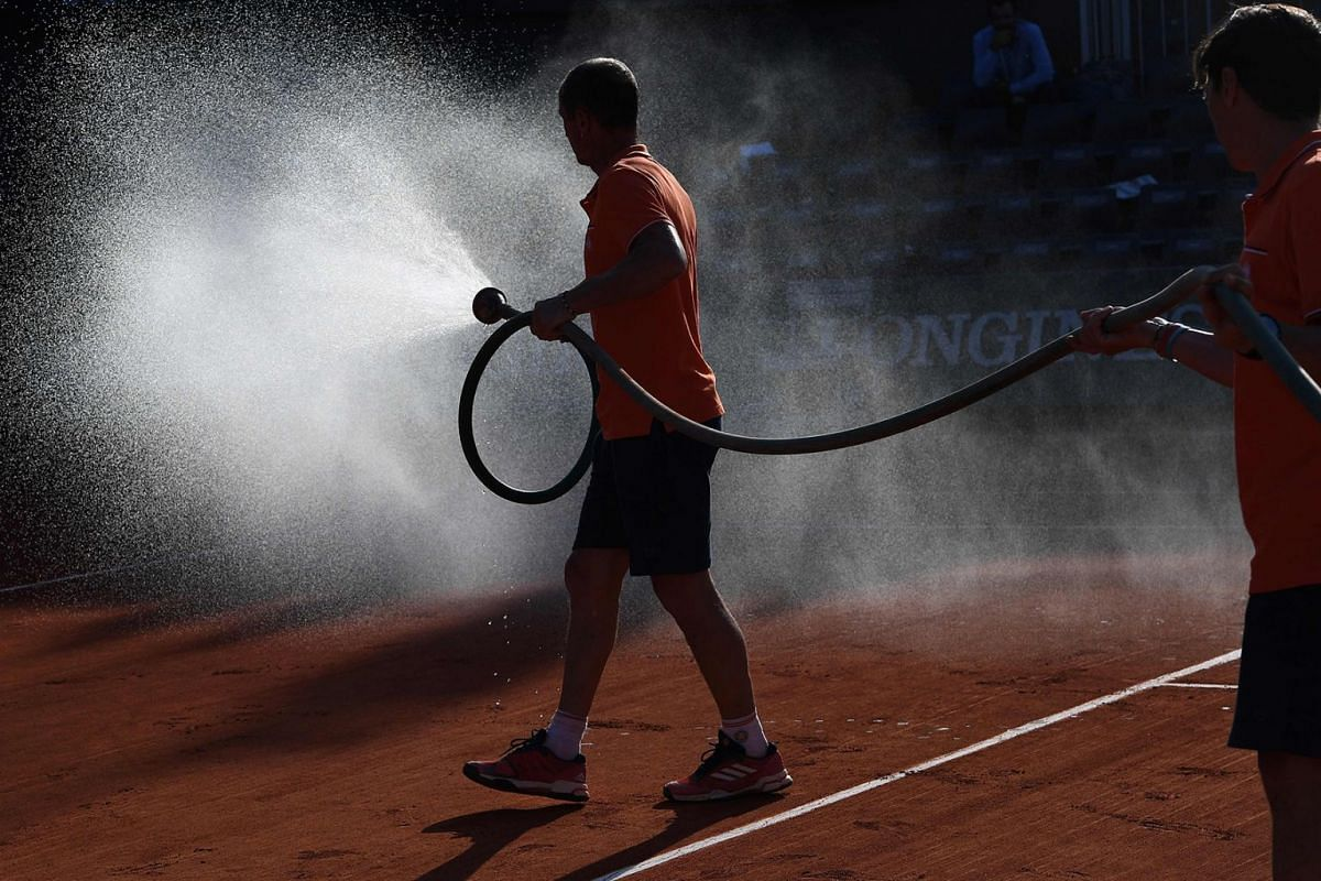 Groundstaff members water the court during a break on day three of The Roland Garros 2018 French Open tennis tournament in Paris on May 29, 2018. Photo: AFP
