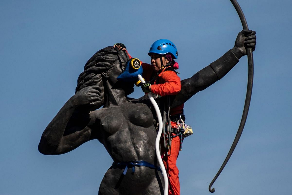 An activist of the environmental organization Greenpeace installs an oxygen tank and mask on the La Diana Cazadora monument to protest poor air quality and excessive pollution in Mexico, in Mexico City on May 30, 2018. Photo: AFP