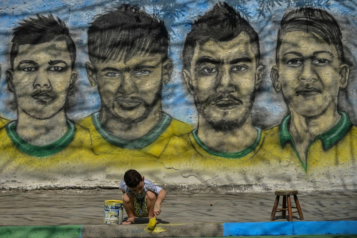 A boy paints the kerb with the Brazilian colours close to a graffiti showing Brazilian football players taking part in the upcoming 2018 World Cup, in Camboata neighbourhood in Rio de Janeiro, Brazil, on May 31, 2018. Photo: AFP