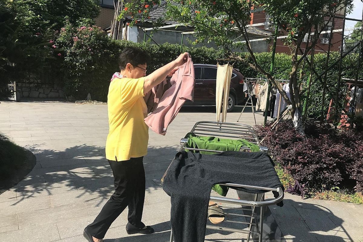 Madam Wang Guifen hangs her clothes to dry. While a hired cleaner cleans the house twice a week, simple chores are done by the Zhus and the tenants. Mealtimes are a lively, social affair, and there is a good spread of vegetables, meat, poultry and se