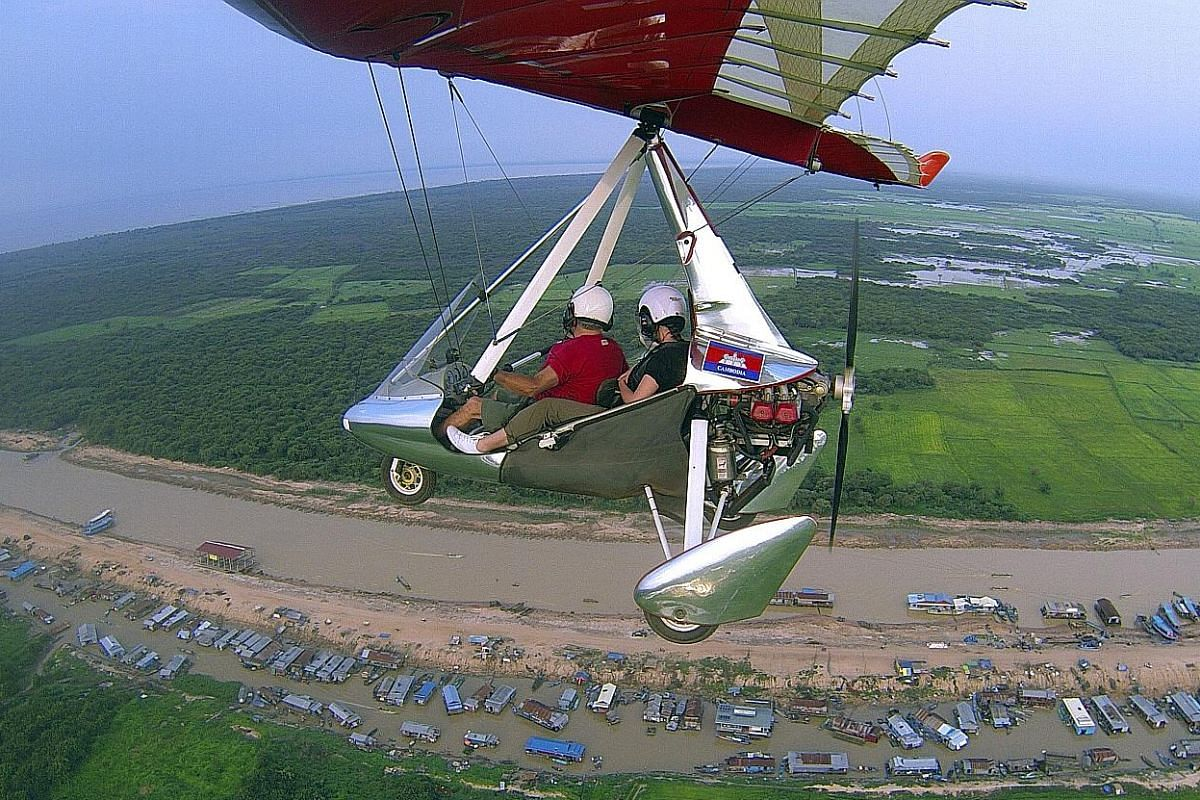 Riding a microlight aircraft, tourists can fly over Tonle Sap (top) and get a bird's-eye view of Angkor Wat (above).