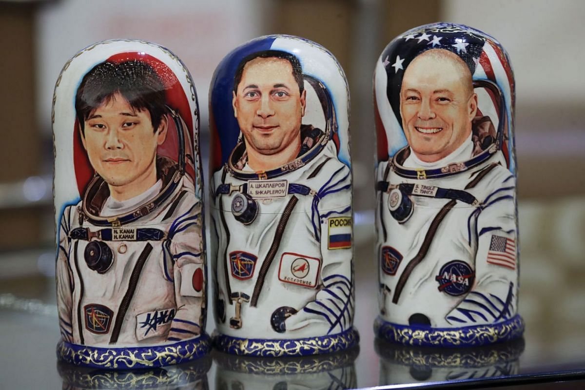 Matryoshka, Russian traditional wooden dolls, decorated with portraits of US astronaut Scott Tingle (R), Russian cosmonaut Anton Shkaplerov (C) and Japanese astronaut Norishige Kanai (L) are displayed during a welcome ceremony at the airport of Karag
