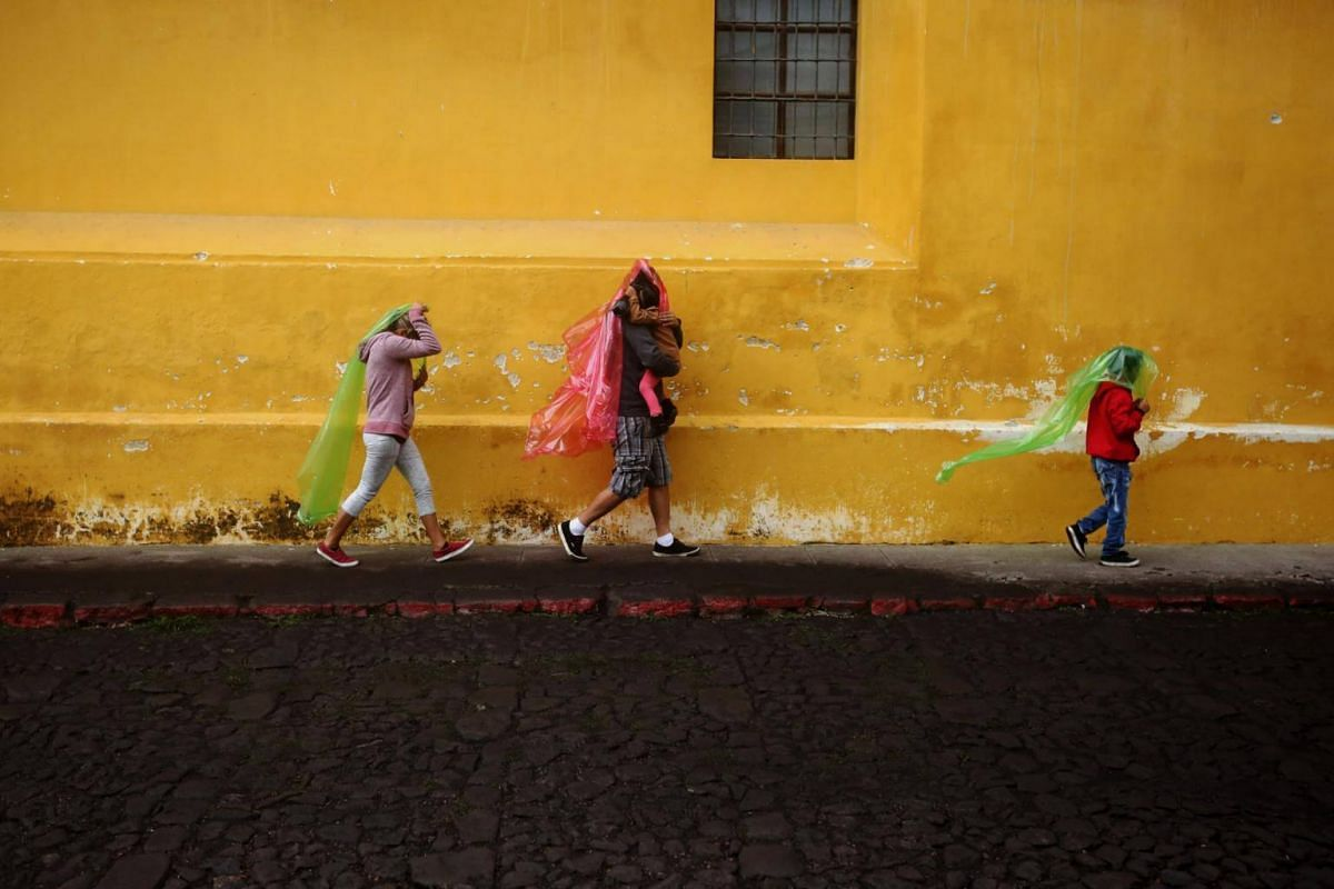 Members of a family cover themselves to avoid ashes in Antigua Guatemala, Sacatepequez, on June 3, 2018.