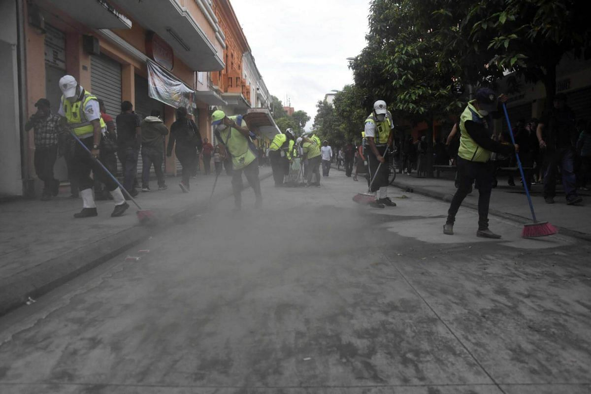 Municipal employees sweep up ash in Guatemala City, on June 3, 2018.