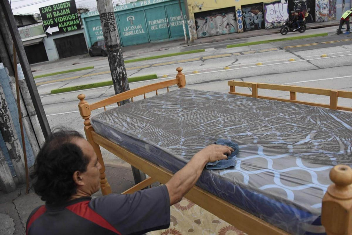 A man cleans the ash that fell on a bed for sale on a street in Guatemala City, on June 3, 2018.