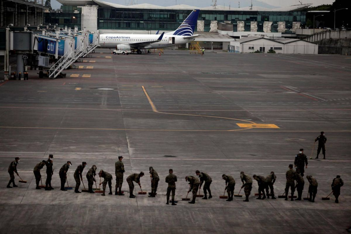 Soldiers sweep the ash covered tarmac at La Aurora International Airport after Fuego volcano erupted in Guatemala City, on June 3, 2018.