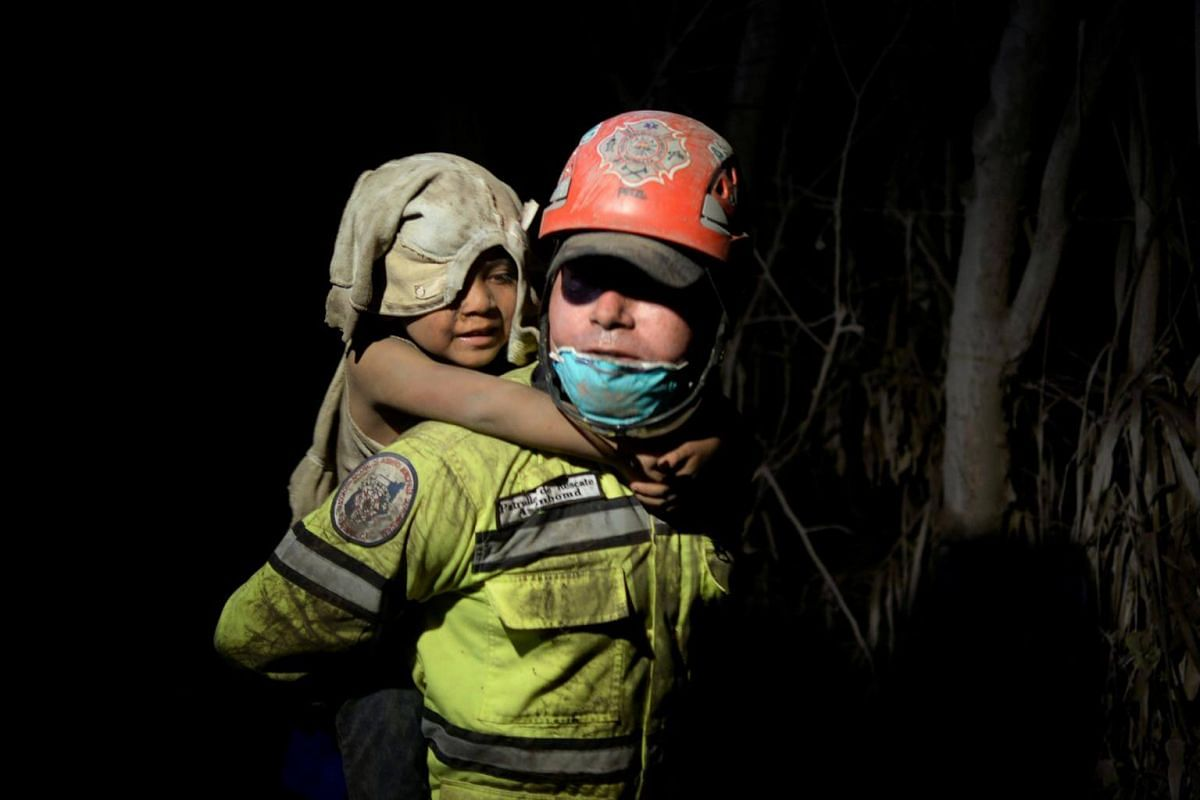 A rescue worker carries a child covered in ash after Fuego volcano erupted  in El Rodeo, Guatemala, on June 3, 2018.