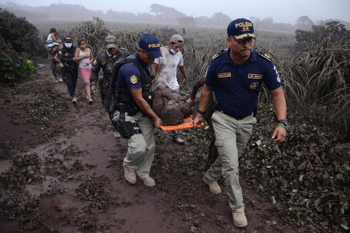 Police officers carry a wounded man after the eruption of the Fuego Volcano, in El Rodeo village, on June 3, 2018.