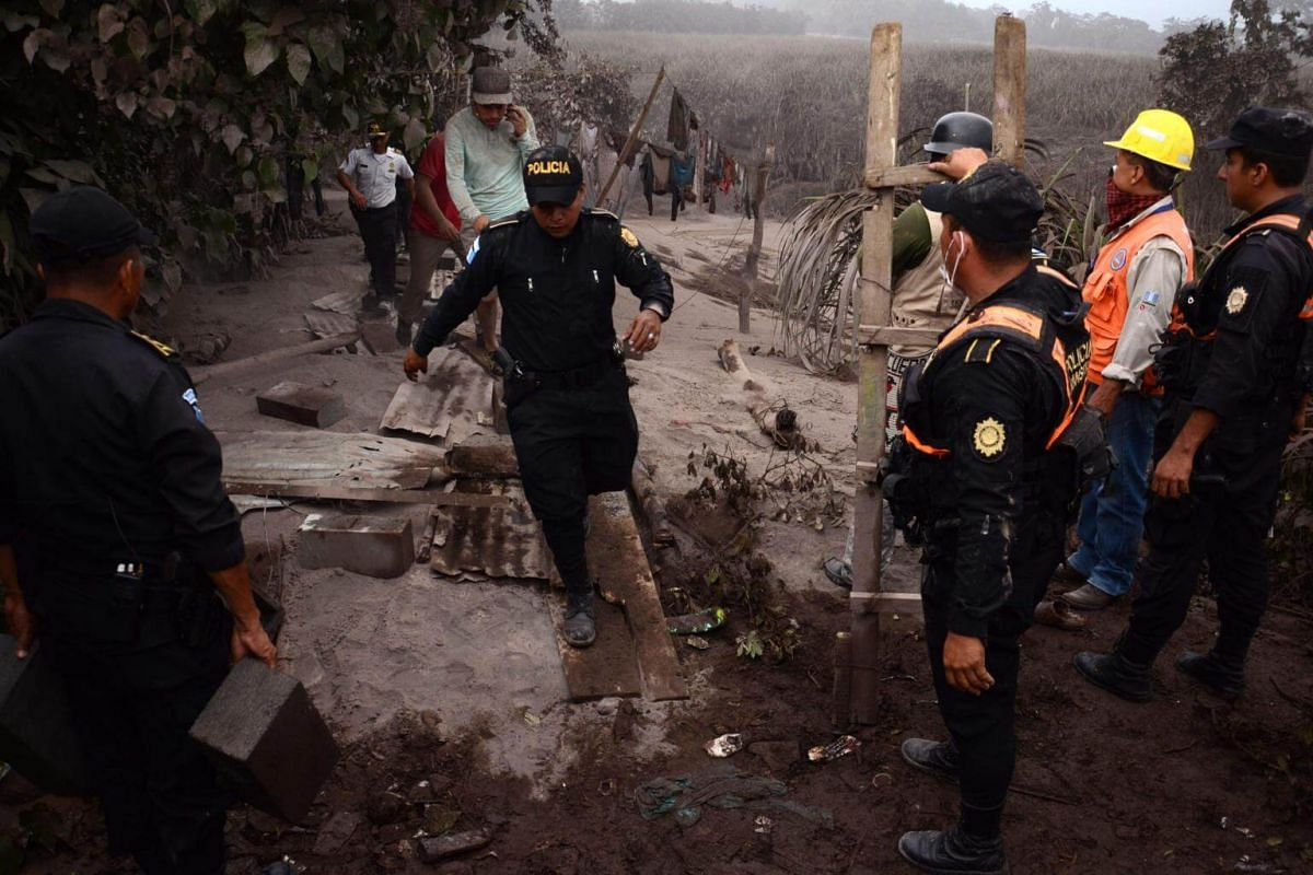 Police officers work in El Rodeo village after the eruption of the Fuego Volcano, on June 3, 2018.