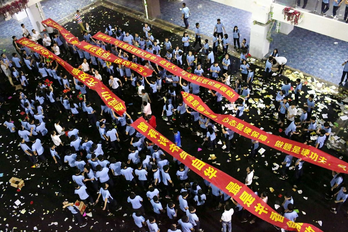 """This photo taken on June 4, 2018 shows high school students taking part in a rally for relieving stress two days ahead of the upcoming annual """"Gaokao"""" or college entrance examinations in China, in Haikou in China's southern Hainan province. PHOTO: AF"""
