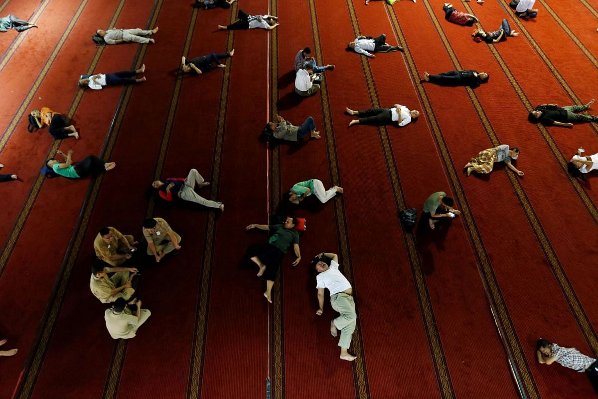 People sleep as they wait for iftar during the holy month of Ramadan at Istiqlal mosque in Jakarta, Indonesia, June 4, 2018. PHOTO: REUTERS