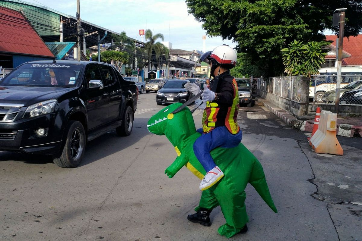Thai police sargent Tanit Bussabong directs traffic wearing a costume where he appears to ride a T-rex dinosaur outside a school in Nakhon Nayok on June 4, 2018. PHOTO: AFP