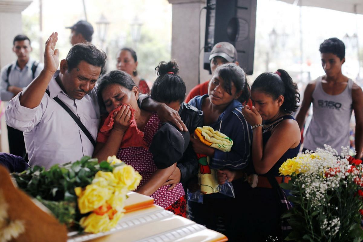 People mourn their loved one, who died during the eruption of the Fuego volcano, during a wake at a plaza in Alotenango, Guatemala, on June 4, 2018.