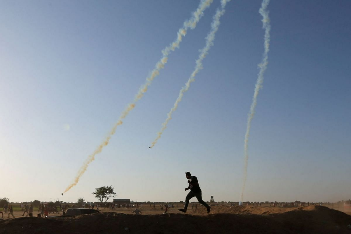 A Palestinian demonstrator runs for cover from tear gas fired by Israeli troops during a protest marking Naksa, at the Israel-Gaza border in the southern Gaza Strip June 5, 2018. PHOTO: REUTERS