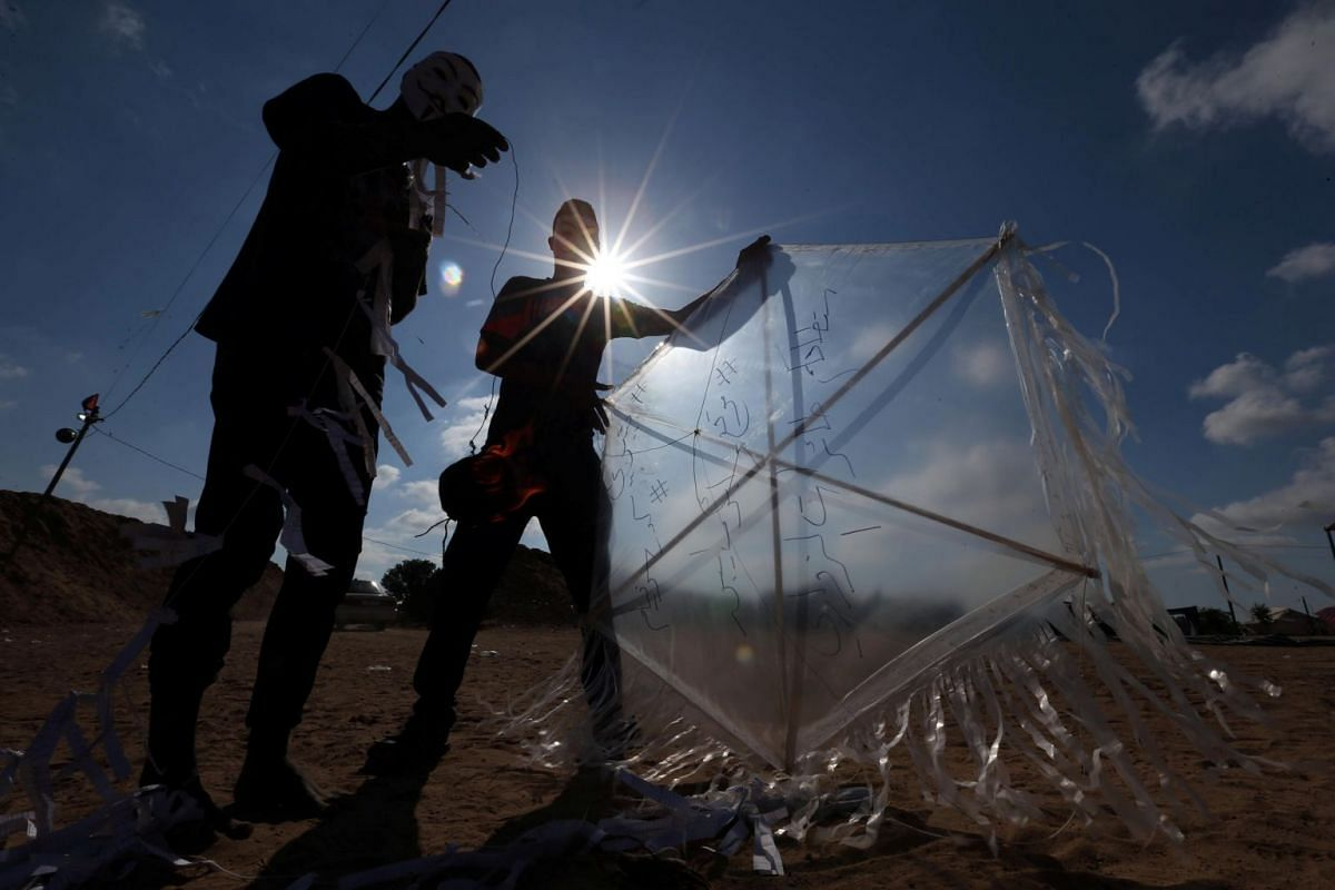 Palestinians prepare to fly a kite loaded with flammable material to be thrown at the Israeli side, near the Israel-Gaza border in the central Gaza Strip, June 4, 2018. Picture taken June 4, 2018. PHOTO: REUTERS
