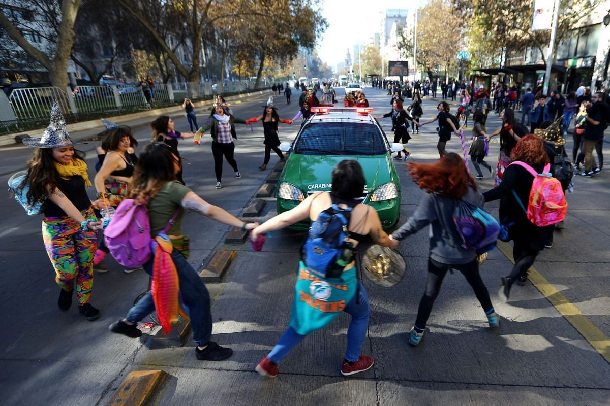 Demonstrators surround a police vehicle during a march demanding an end to sexism and gender violence in Santiago, Chile June 6, 2018. PHOTO: REUTERS