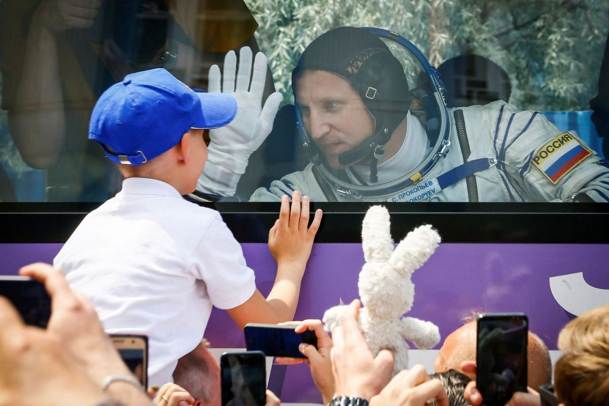 International Space Station (ISS) crew member Sergey Prokopyev of Russia waves to his family from a bus shortly before leaving to board the spacecraft at the Baikonur Cosmodrome, Kazakhstan June 6, 2018. PHOTO: REUTERS