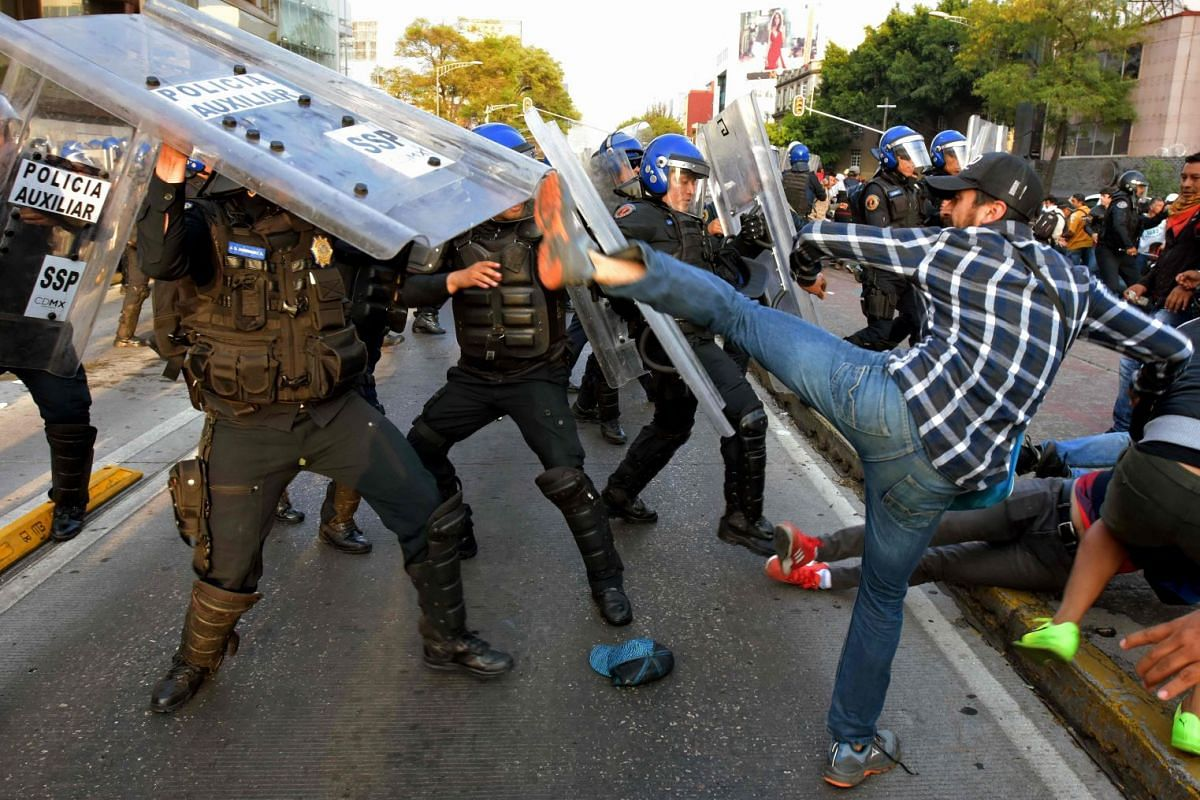 Teachers from across Mexico clash with police during a protest against the education reform and to demand the release of colleagues arrested in previous protests, in front of television station Televisa, in Mexico City on June 07, 2018. PHOTO: AFP