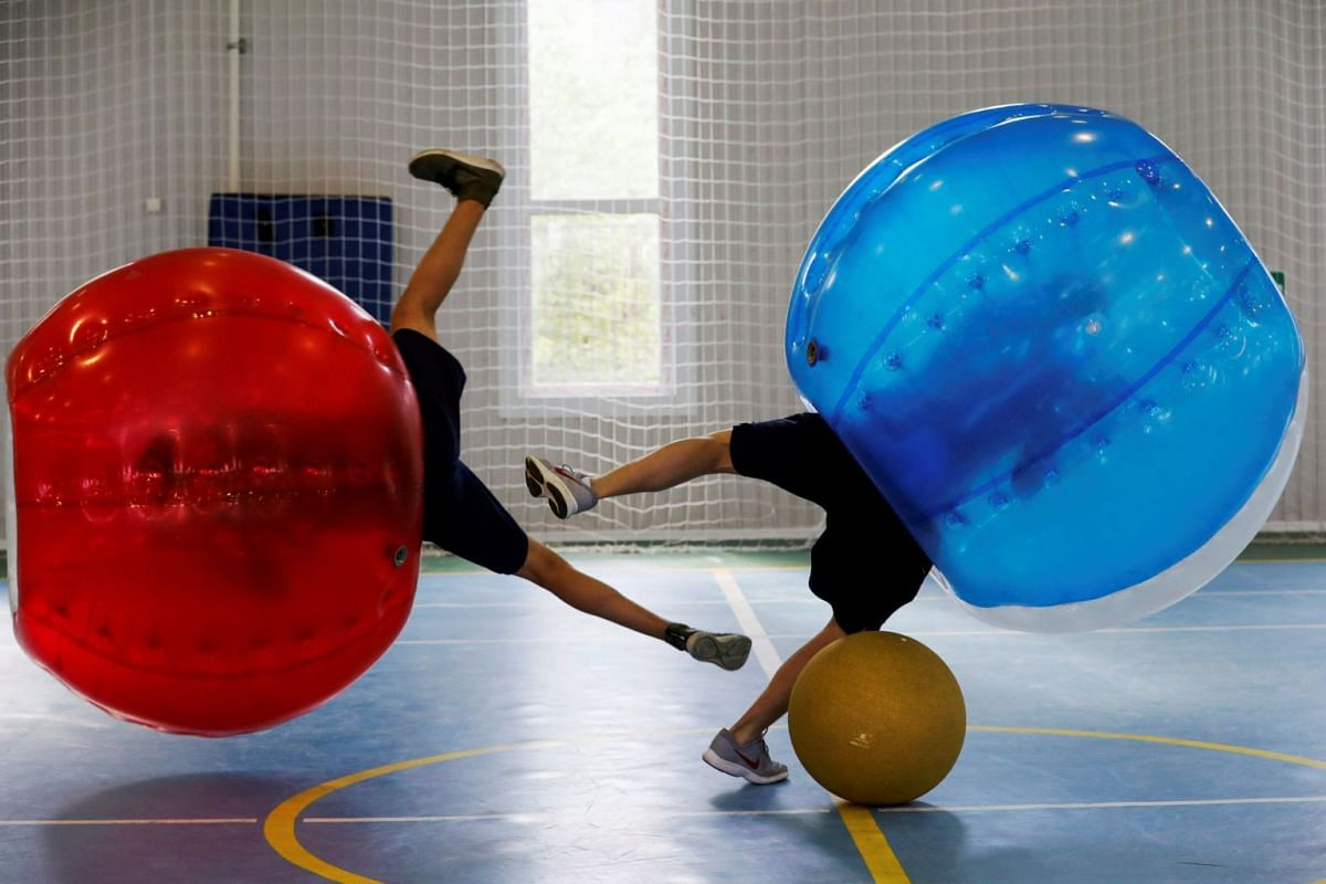 Schoolchildren play bumper ball, the game involving strapping football players into giant inflatable balls, at a sports facility in Moscow, Russia May 12, 2018. Picture taken May 12, 2018. PHOTO: REUTERS