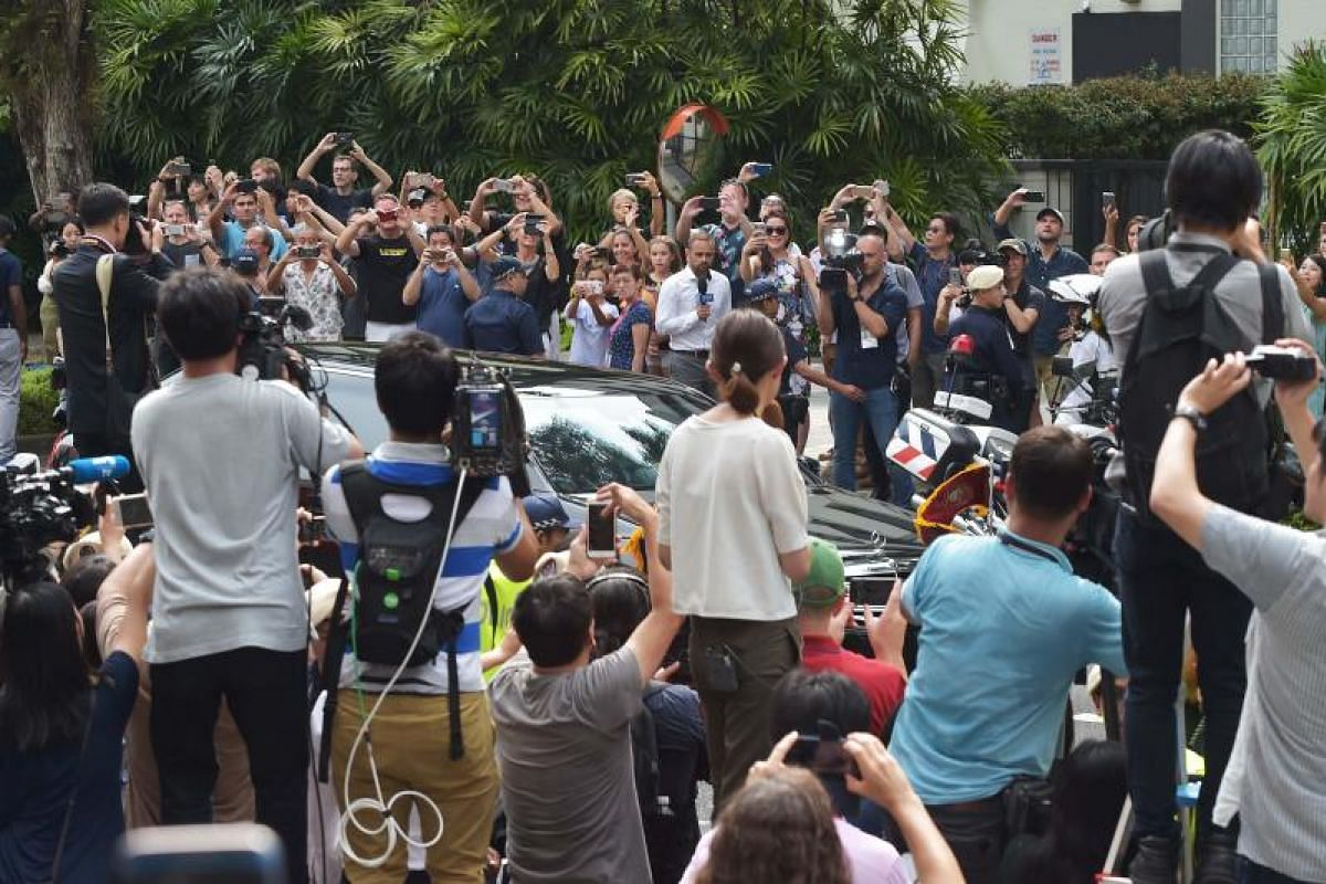 Members of the media and the public watch as Mr Kim's motorcade arrives at The St Regis.